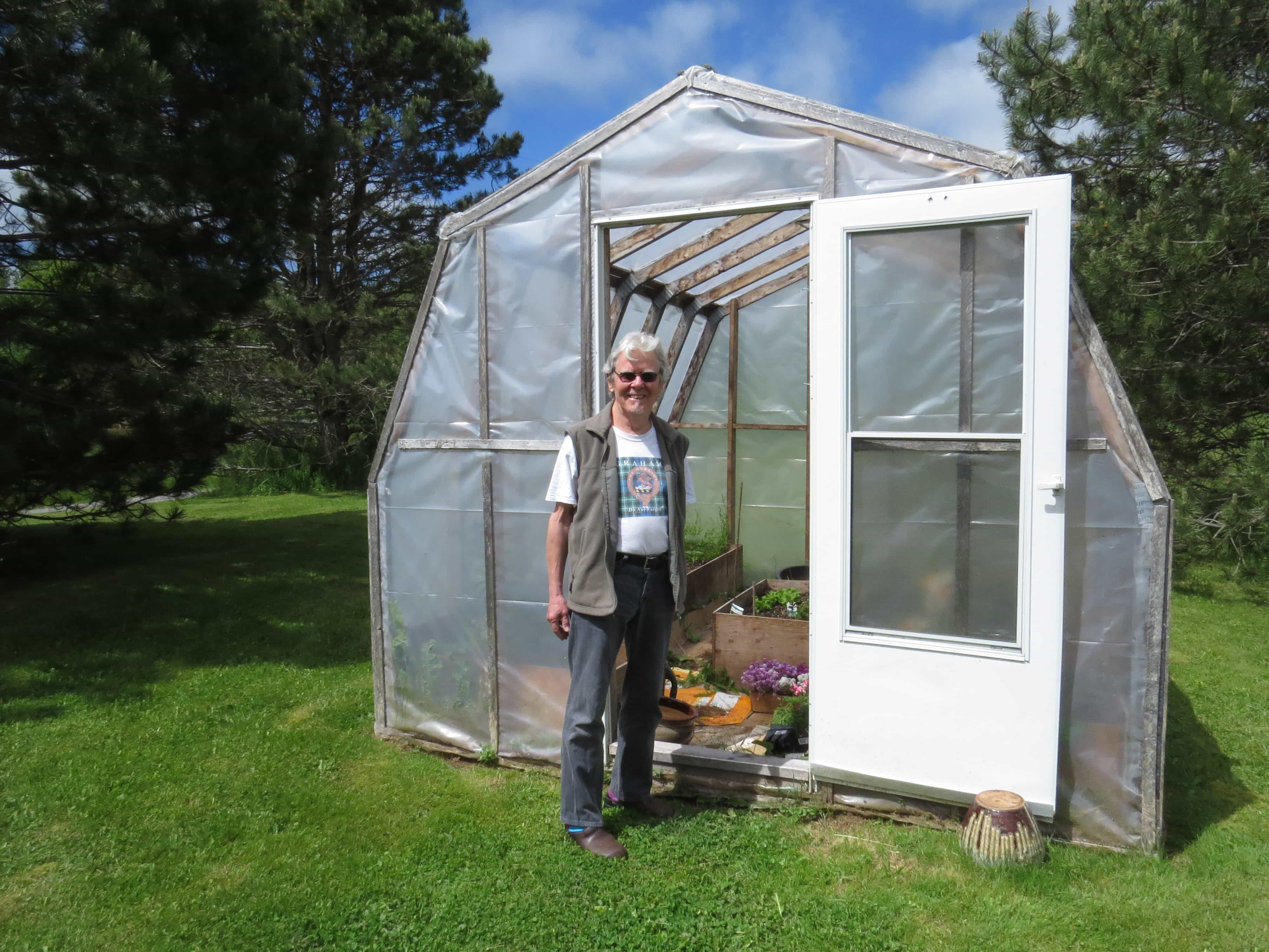 John Graham-Pole working in his greenhouse